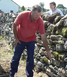Dry Stone Walliing Workshop with Steve Allen at Greystoke Cycle Cafe - Steve points out to the group the parts he is most impressed with- the choice of stone is everything